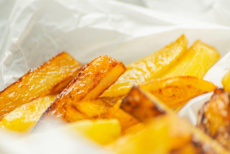 Il primo piano delle fritture dorate ha preparato dalle patate fresche, grasse ma fotografia stock libera da diritti