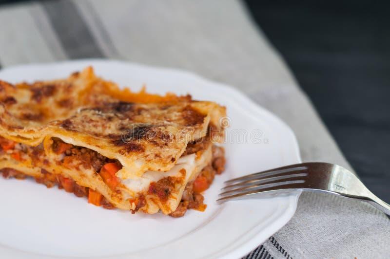 Il primo piano delle lasagne al forno tradizionali fatte con la salsa bolognese del manzo è servito su un piatto bianco fotografia stock