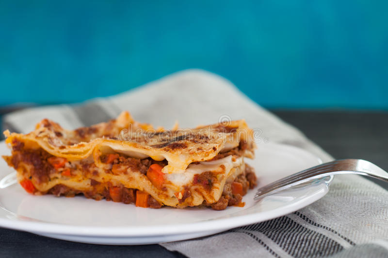 Il primo piano delle lasagne al forno tradizionali fatte con la salsa bolognese del manzo è servito su un piatto bianco immagini stock libere da diritti
