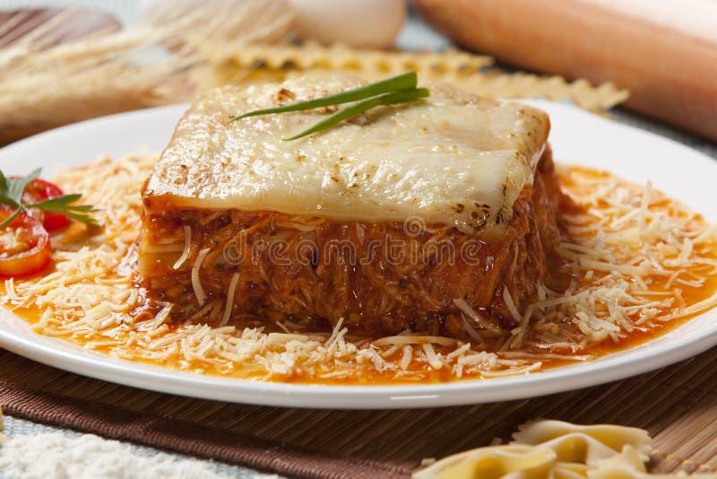 Il primo piano delle lasagne al forno tradizionali fatte con la salsa bolognese del manzo tritato completata con le foglie del ba immagini stock