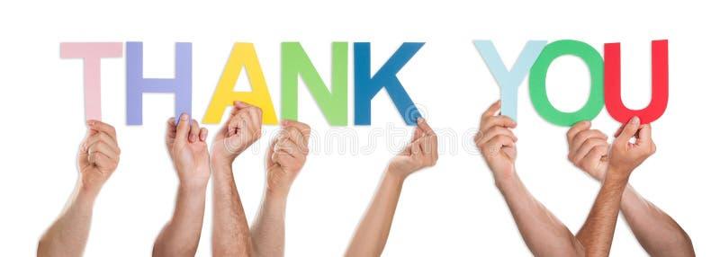 Il primo piano delle mani che tengono la parola vi ringrazia immagine stock