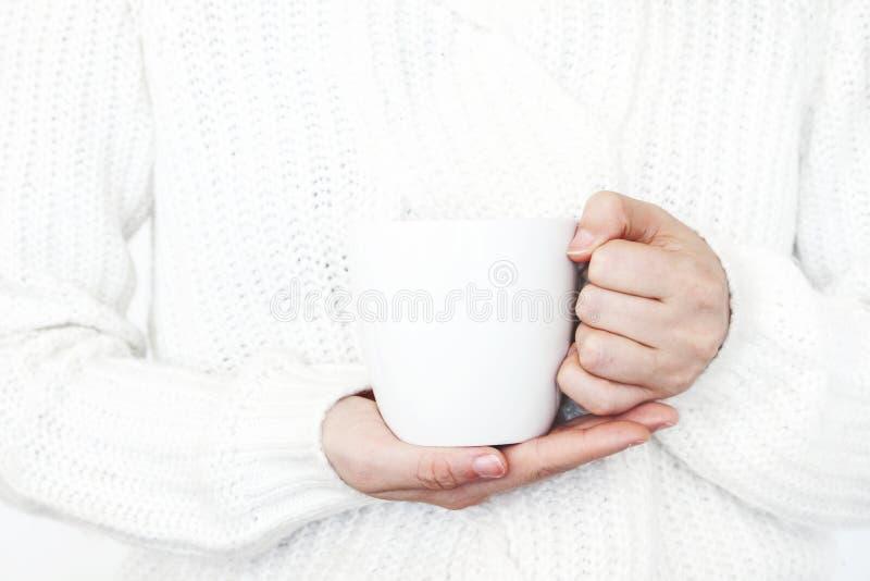 Il primo piano delle mani del ` s della donna nel bianco ha tricottato il maglione che tiene la tazza di caffè Scena in bianco de fotografia stock libera da diritti