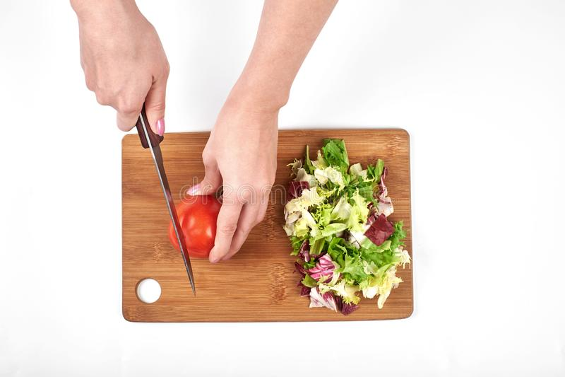 Il primo piano delle mani della donna che affettano l'insalata e le verdure su un bordo di legno, isolato su fondo bianco, copia  fotografie stock libere da diritti