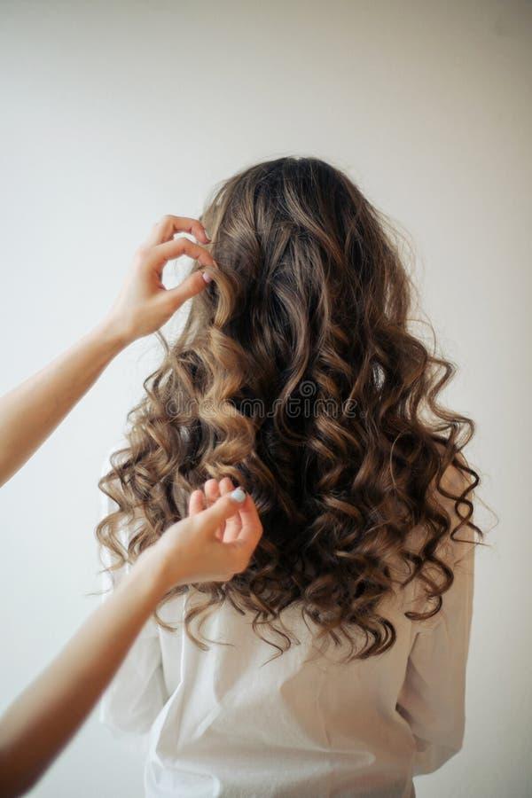 Il primo piano delle mani femminili del parrucchiere o del coiffeur fa l'acconciatura fotografie stock