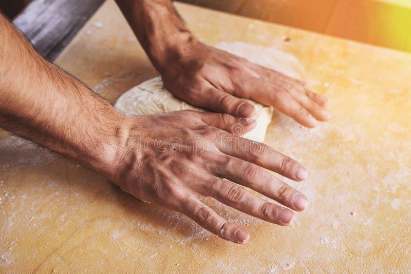 Il primo piano dello srotolamento delle mani degli uomini, prepara la base per pizza fotografia stock