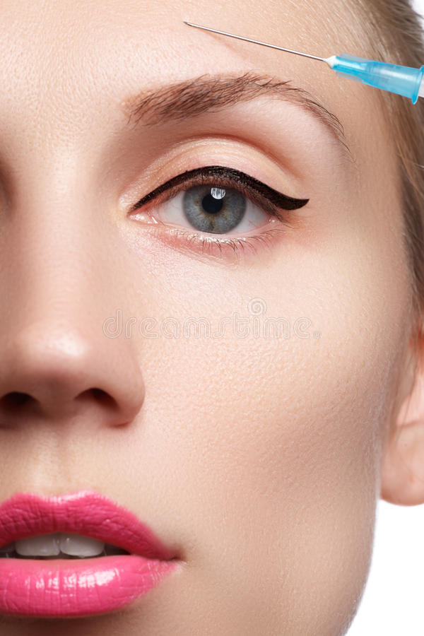 Il primo piano di bella donna ottiene l'iniezione Bello fronte e la siringa (concetto dell'iniezione del cosmetico e della chirur immagine stock libera da diritti