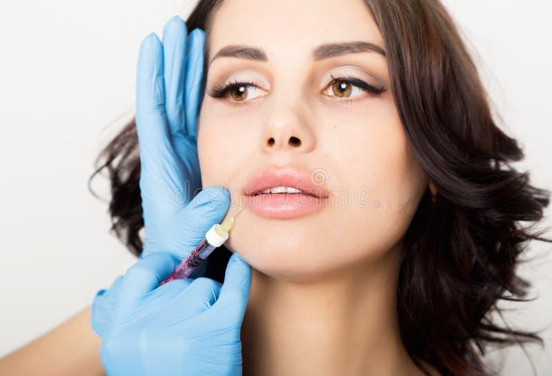 Il primo piano di bella giovane donna ottiene l'iniezione nell'area delle labbra e dell'occhio dall'estetista Concetto di cosmeto immagini stock