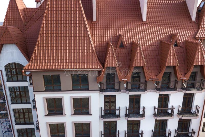 Il primo piano di esterno di costruzione della facciata con la parete dello stucco, le inferriate del balcone del ghisa, il tetto fotografia stock