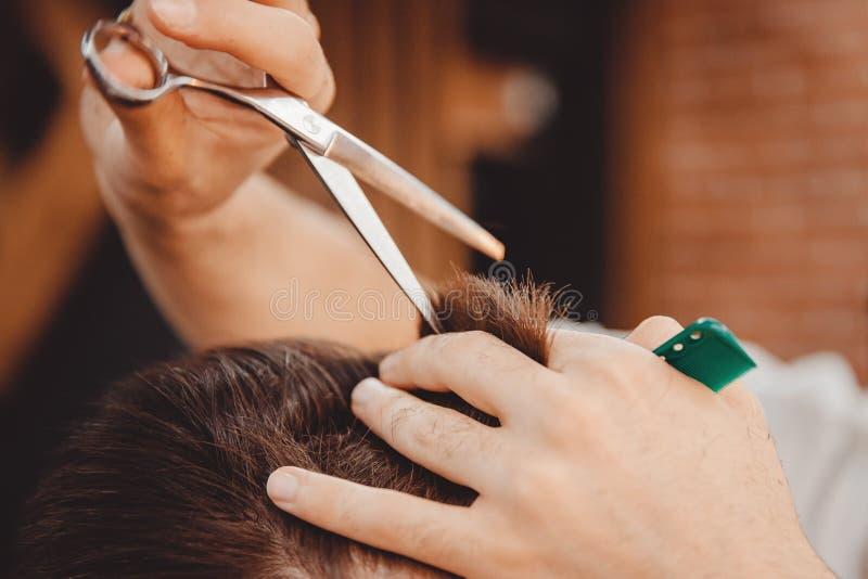 Il primo piano di taglio di capelli dell'uomo, padrone fa i capelli che disegnano nel negozio di barbiere immagine stock