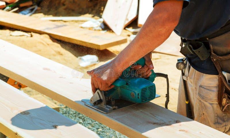 Il primo piano di un carpentiere che usando una circolare ha visto per tagliare un grande bordo di legno immagini stock libere da diritti