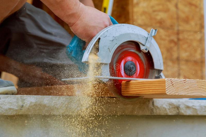 Il primo piano di un carpentiere che usando una circolare ha visto per tagliare un grande bordo di legno immagine stock libera da diritti
