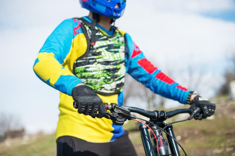 Il primo piano di un ciclista del mtb del corridore dell'uomo della mano nei guanti di sport che si prepara per una corsa tiene s fotografia stock libera da diritti