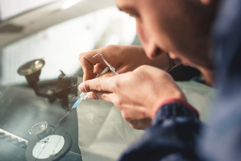 Il primo piano di un riparatore professionista del parabrezza riempie una crepa nel vetro di polimero speciale tramite una siring immagini stock libere da diritti