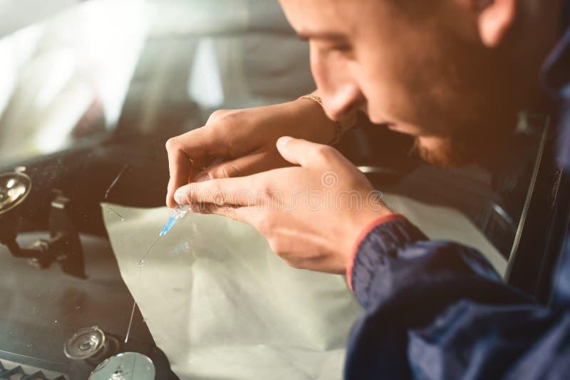Il primo piano di un riparatore professionista del parabrezza riempie una crepa nel vetro di polimero speciale tramite una siring immagine stock libera da diritti