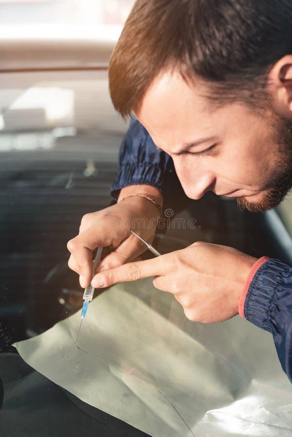 Il primo piano di un riparatore professionista del parabrezza riempie una crepa nel vetro di polimero speciale tramite una siring fotografia stock libera da diritti