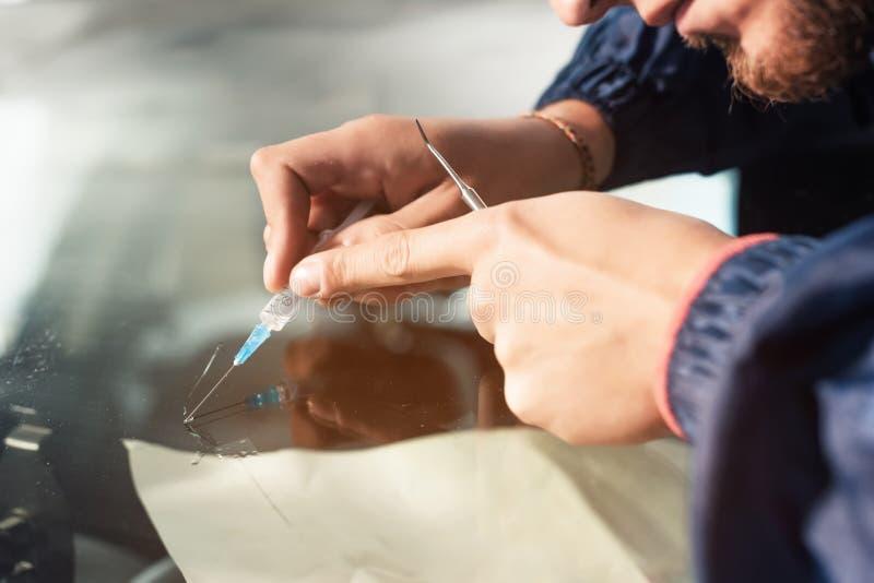Il primo piano di un riparatore professionista del parabrezza riempie una crepa nel vetro di polimero speciale tramite una siring fotografia stock