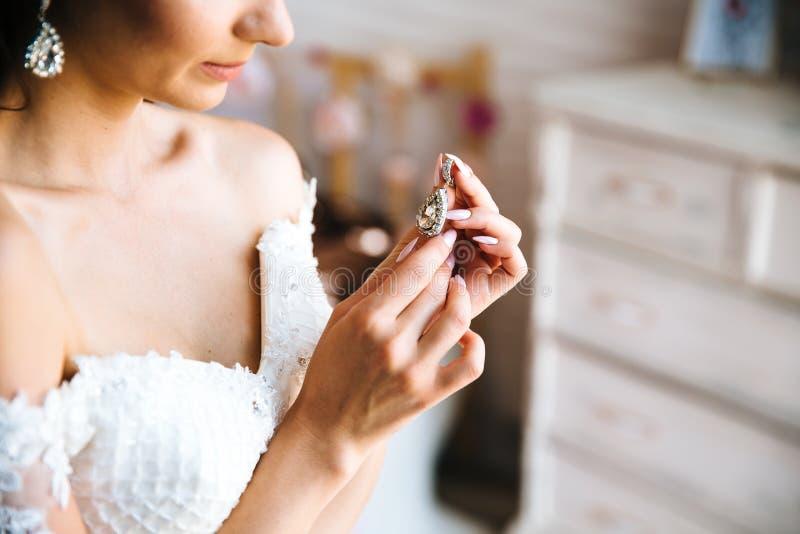 Il primo piano di un telaio potato di una ragazza in un vestito da sposa esamina un orecchino Manicure della sposa, decorazioni fotografie stock