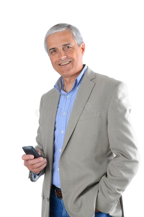 Il primo piano di un uomo d'affari maturo si è vestito con indifferenza e tenendo un dispositivo cellulare in sua mano fotografia stock