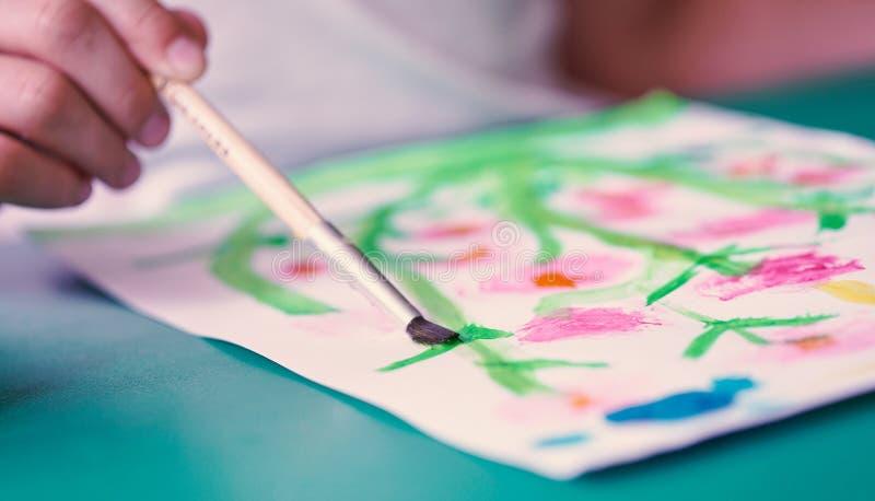 Il primo piano di una spazzola nella mano di un disegno del piccolo bambino fiorisce con gli acquerelli variopinti Scuola, concet fotografia stock
