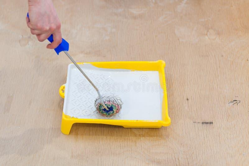 Il primo piano di uomo le mani facendo uso del rullo di pittura mentre lavora all'interno immagine stock