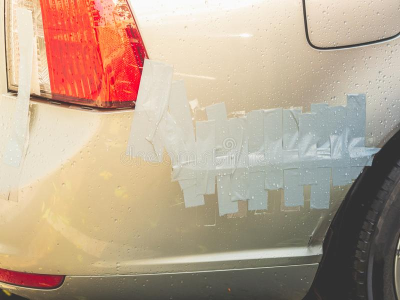 Il primo piano ha danneggiato il paraurti dell'automobile riparato dal nastro di condotta immagini stock
