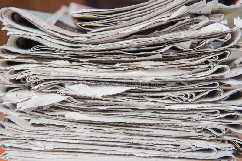 Il primo piano ha impilato ed accatastato sui giornali per fondo fotografia stock