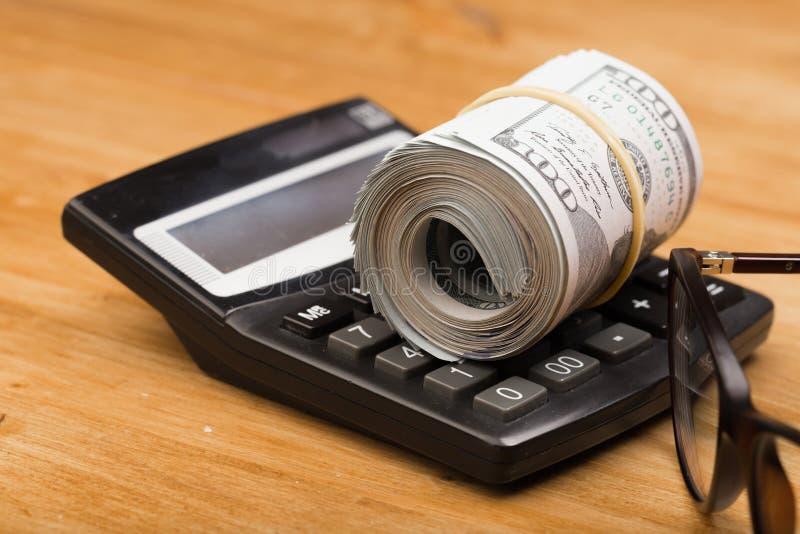 Il primo piano ha rotolato le banconote americane dei dollari con i vetri del ANG del calcolatore immagine stock
