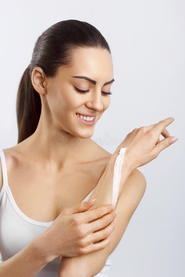 Il primo piano ha sparato delle mani della donna che applicano la crema per le mani d'idratazione Belle mani della donna con crem fotografie stock libere da diritti