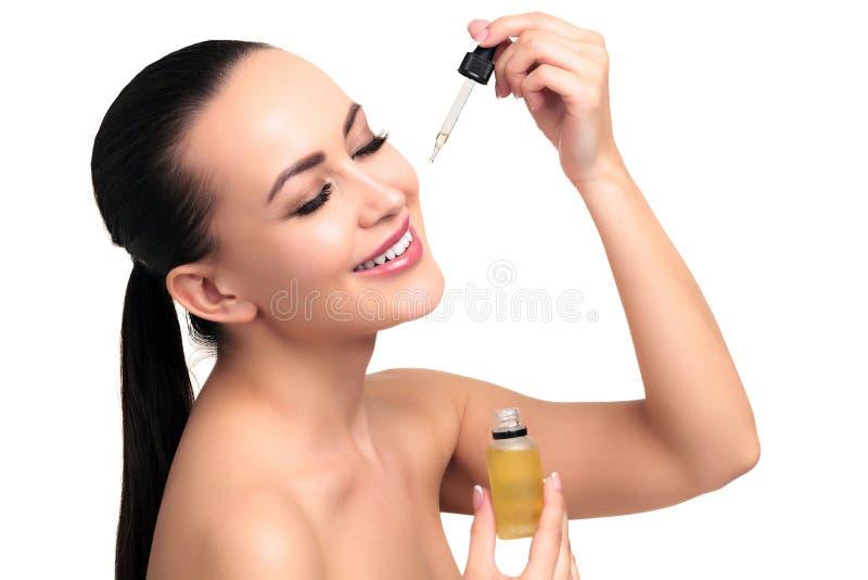 Il primo piano ha sparato di olio cosmetico che si applica sul fronte del ` s della giovane donna immagini stock libere da diritti