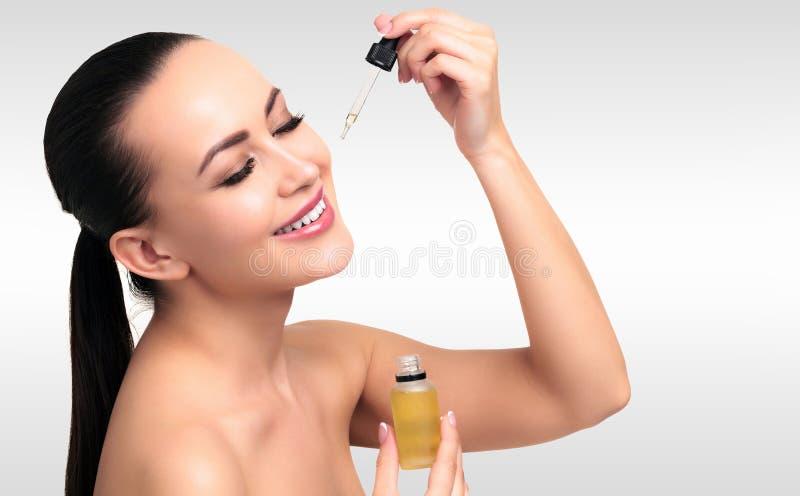 Il primo piano ha sparato di olio cosmetico che si applica sul fronte del ` s della giovane donna immagine stock