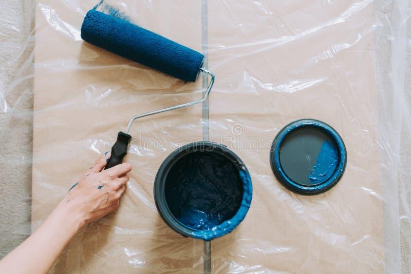 Il primo piano ha sparato di una femmina facendo uso dei rulli di pittura con il blu di colore fotografia stock libera da diritti