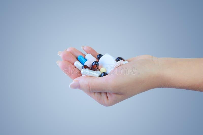 Il primo piano ha sparato di una mano che tiene le pillole di colore su fondo blu fotografie stock libere da diritti