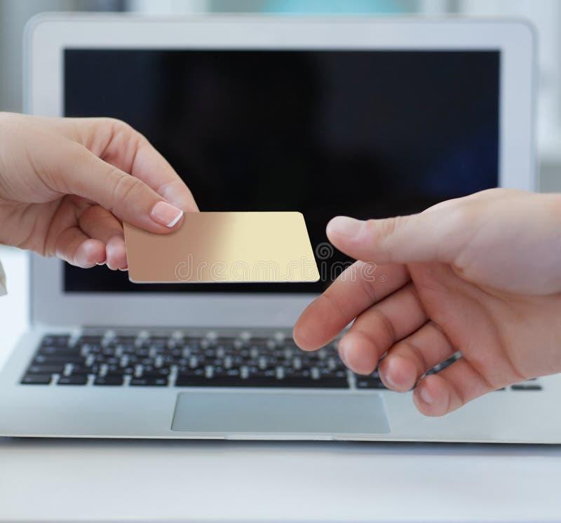 Il primo piano ha sparato di una mano del ` s della donna che dà una carta di credito di pagamento al venditore nel deposito di c immagini stock