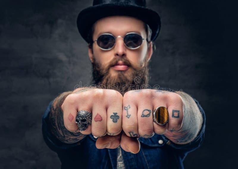 Il primo piano ha tatuato le dita del ` s dei pantaloni a vita bassa con gli anelli fotografia stock libera da diritti