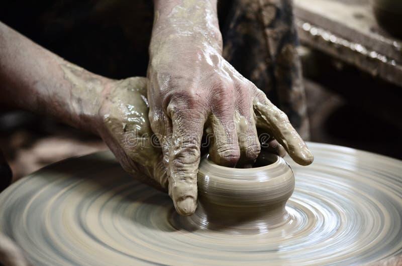 Il primo piano sull'uomo del vasaio passa la modellatura del mestiere ceramico fotografie stock