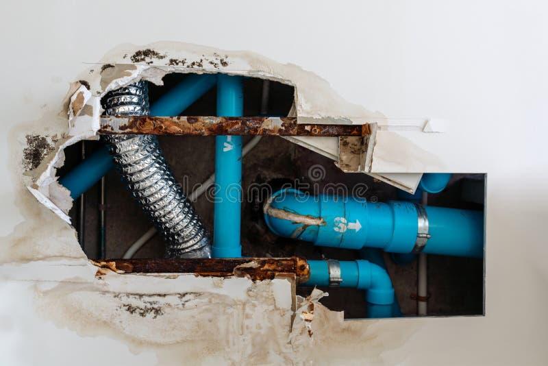 Il problema residenziale domestico, soffitto di danno in toilette, l'acqua perde dalla rete di tubazioni residua fa il soffitto n fotografia stock