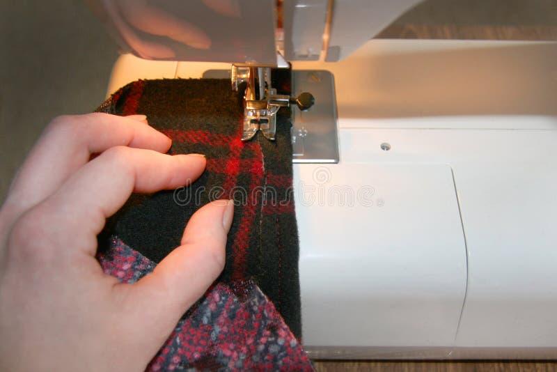 Il processo del cucito dei prodotti, la ragazza esegue la linea sulla macchina, la mano tiene un tessuto immagini stock
