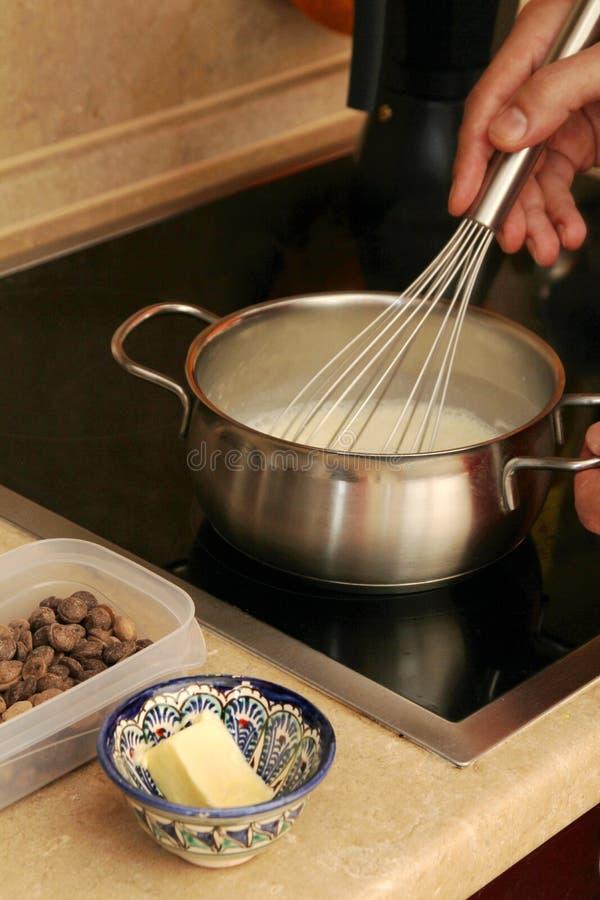 Il processo di cottura della crema del cioccolato al latte per sachertorte tradizionale immagini stock