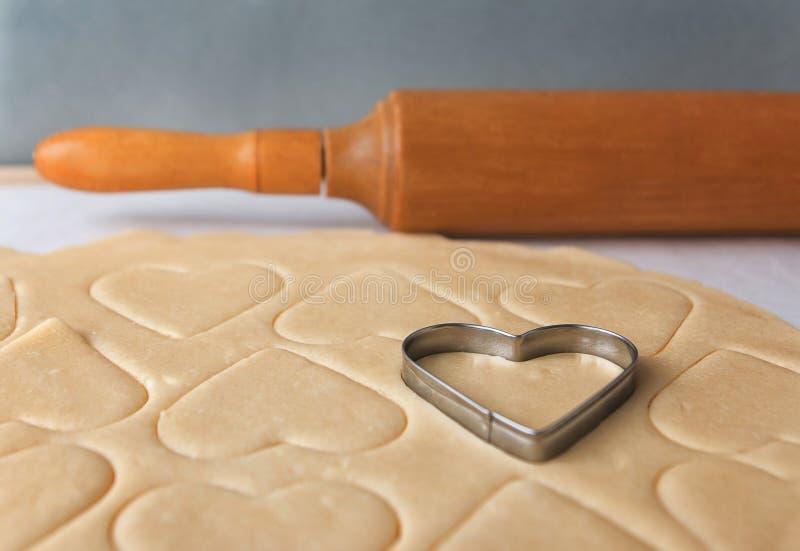 Il processo di cuocere i biscotti nel paese Il cuore ha modellato le taglierine del biscotto che tagliano i biscotti di zucchero  fotografia stock libera da diritti