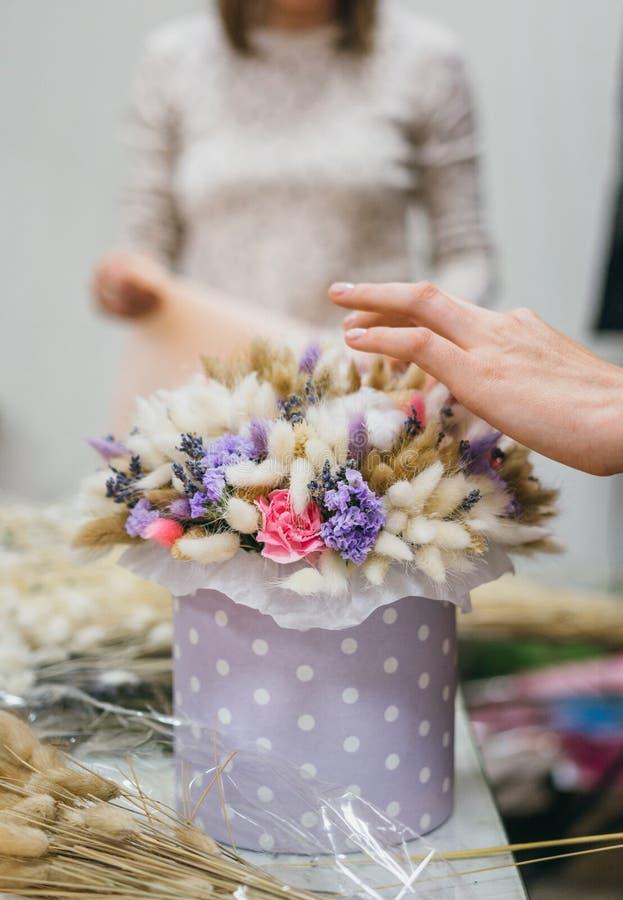 Il processo di fabbricazione del mazzo Mazzo variopinto dei fiori secchi differenti del ramo secco dei fiori nelle mani del fiori fotografia stock libera da diritti