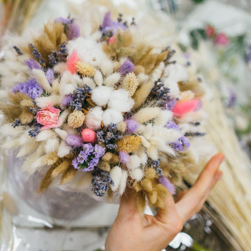 Il processo di fabbricazione del mazzo Mazzo variopinto dei fiori secchi differenti del ramo secco dei fiori nelle mani del fiori fotografie stock
