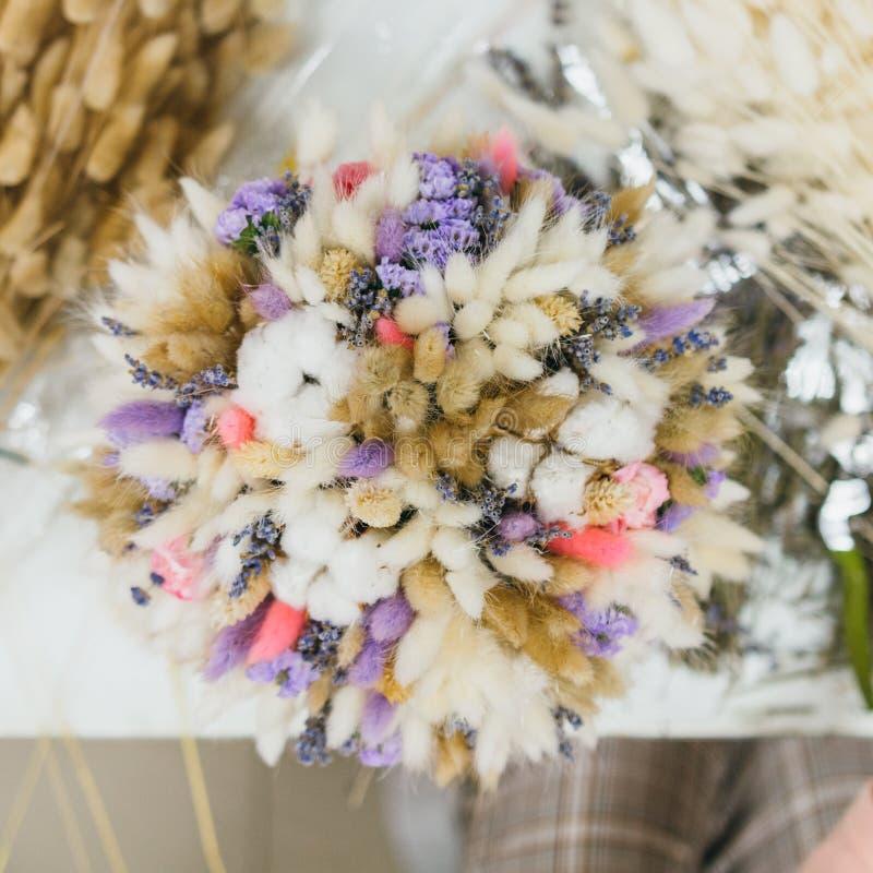 Il processo di fabbricazione del mazzo Mazzo variopinto dei fiori secchi differenti del ramo secco dei fiori nelle mani del fiori immagini stock libere da diritti