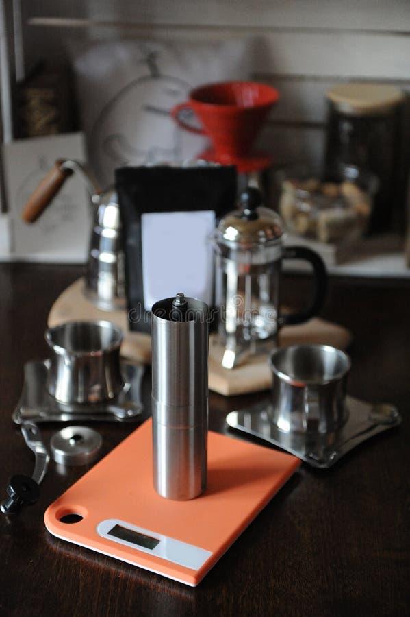 Il processo di fare caffè Il macinacaffè sulle scale, francese preme e gocciola il creatore Pacchetto con l'etichetta in bianco immagine stock