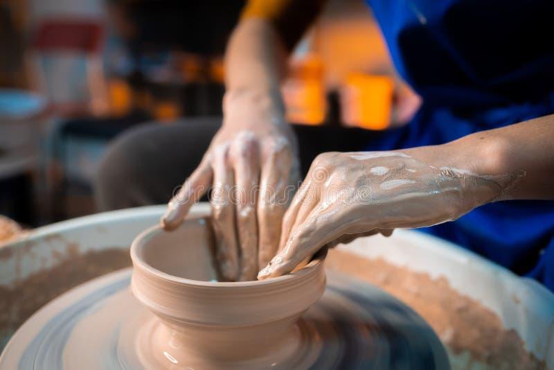 Il processo di lavoro del lavoro dell'uomo a tornio da vasaio nello studio di arte L'artigiano sconosciuto crea la brocca Fuoco s immagini stock libere da diritti