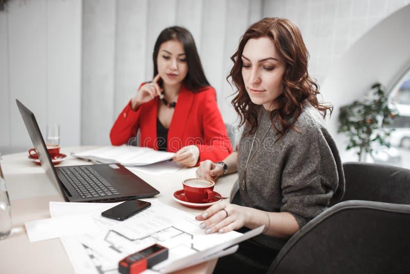 il processo di lavoro I progettisti stanno lavorando con il computer portatile e la documentazione al progetto interno immagini stock