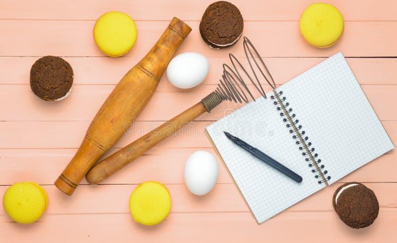 Il processo di produrre i biscotti del cioccolato, maccheroni, ingredienti su un fondo di legno rosa Uova, matterello, corolla immagini stock