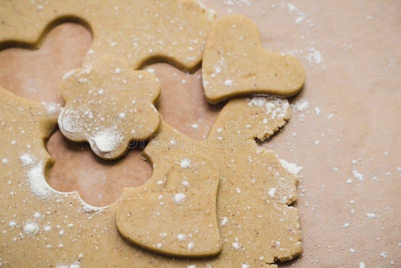 Il processo di produrre i biscotti dello zenzero sotto forma di cuore e di fiore, pan di zenzero immagine stock libera da diritti