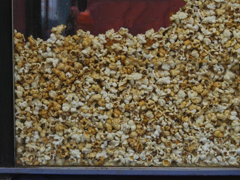 Il processo di produrre popcorn salato in un apparato speciale immagini stock