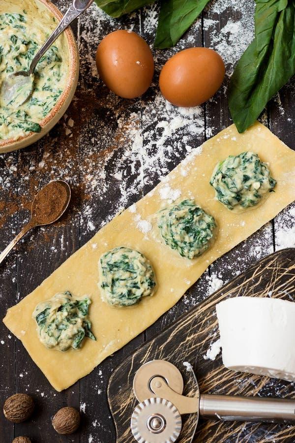 Il processo di produrre ravioli con la ricotta, gli spinaci e la noce moscata fotografie stock libere da diritti