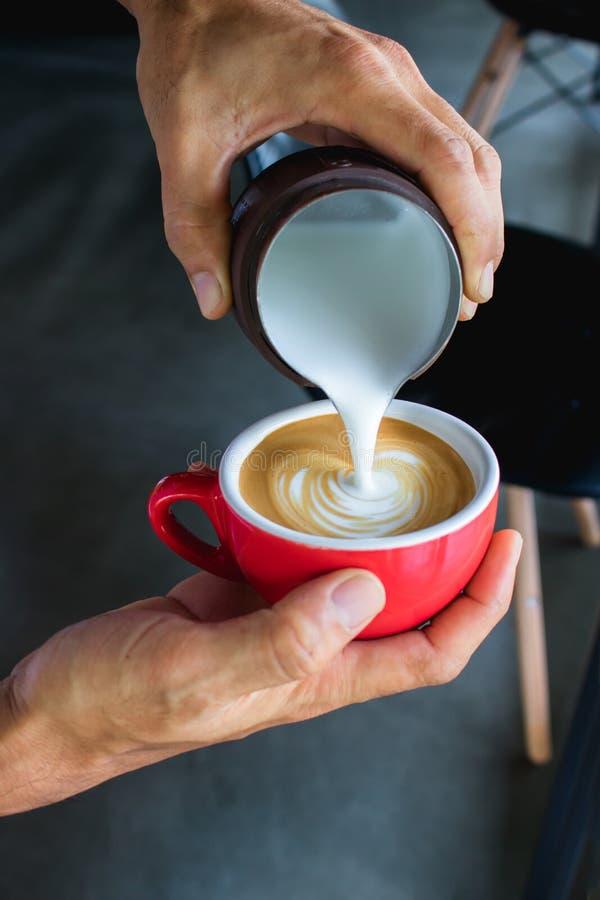 Il processo di versamento del latte dal lanciatore fa l'arte del latte del caffè da Baris fotografie stock